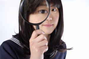 虫眼鏡を持つ女子高生