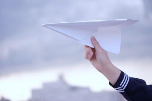 紙飛行機を持つ女子高生の手