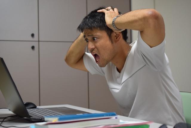 パソコンを見て頭を抱える男性